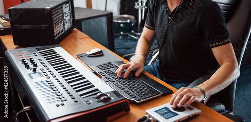 Fototapeta Sound engineer in headphones working and mixing music indoors in the studio obraz