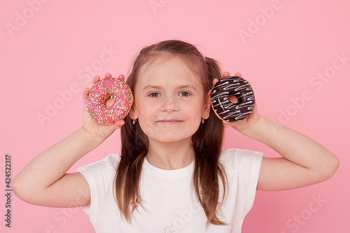 Young beautiful caucasian girl holding tasty colorful doughnuts afraid and shocked with surprise and amazed expression, fear and excited face Fototapet