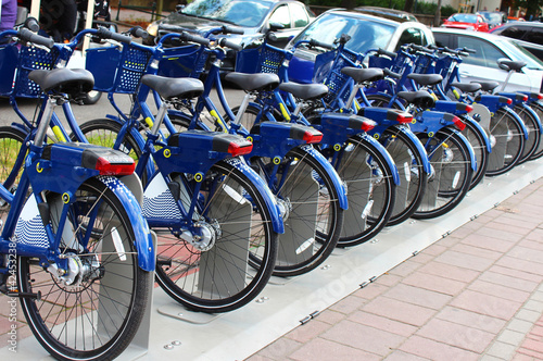 Fotografia, Obraz Blue city bikes in Poland, parked in a row, ready for citizens and tourists, where everyone can rent public bikes