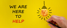Support Symbol. Businessman Writing 'we Are Here To Help', Isolated On Beautiful Yellow Background. Light Bulb Icon. Business And Support Concept. Copy Space.