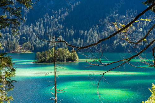 Tela Faboulus landscape of Eibsee Lake with turquoise water in front of Zugspitze summit under sunlight