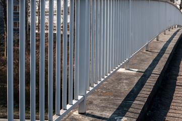 a white painted metal railing at a footbridge