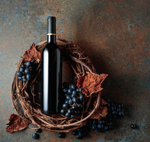 Bottle Of Red Wine With Grapes And Dried Vine Leaves On An Old Rusty Background.