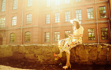Beautiful Girl In Yellow Romantic Dress With Book Near The Vintage Red Brick Wall - Yellow Building. Full Length Woman Read Retro Vintage Book Between Windows