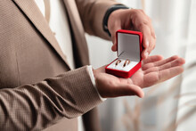 The Man The Groom In A White Shirt And Brown Jacket Holds On His Palm Wedding Gold Rings In A Red Velvet Box By The Window. Groom Morning, Close-up Without A Face Only Hands