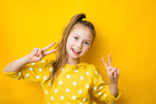 Close Up Studio Photo Portrait Of Sweet Lovely Intelligent With Beaming Smile School Girl Making Giving V-sign Isolated Bright Yellow Background