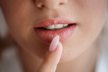 The Bride Girl With Large Magnificent Lips And Healthy White Teeth Presses A Finger With A Long Manicure To Her Mouth. Very Close-up, Macro Shot