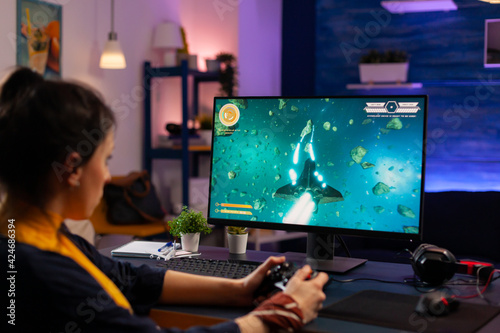 Fototapeta Videogamer playing graphics cyber space sitting on gaming chair using wireless console