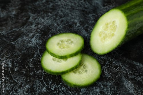 Ripe cucumber and slices on black smoky background Fotobehang