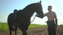 A Man Stands Near A Horse In A Field