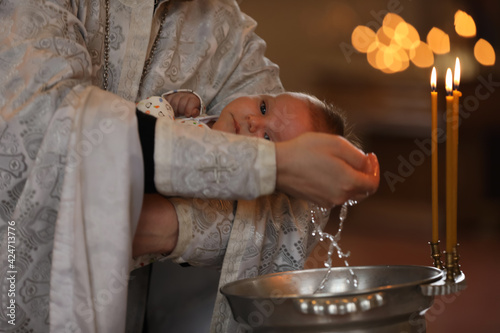 Canvas Priest baptizing adorable baby in church, closeup