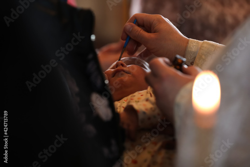 Fotografie, Obraz Woman holding adorable baby in church during baptism ceremony, closeup