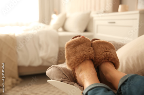 Obraz Woman wearing soft comfortable slippers at home, closeup. Space for text - fototapety do salonu
