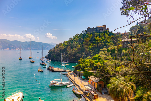 Fototapeta beautiful colorful view Gulf of Portofino Italy with castle Brown in background and boats anchored to small picturesque harbor