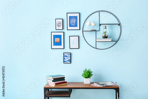 Obraz Books on table near color wall with stylish pictures - fototapety do salonu