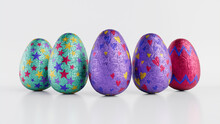 Easter Eggs Isolated Against A White Background. Chocolate Eggs Wrapped In Patterned Cyan, Purple And Red Foil. 3D Render