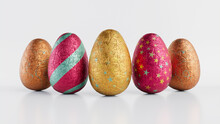 Easter Eggs Isolated Against A White Background. Chocolate Eggs Wrapped In Patterned Gold, Red And Silver Foil. 3D Render
