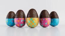 Easter Eggs Isolated Against A White Background. Partially Unwrapped Chocolate Eggs With Patterned Blue, Orange And Pink Foil. 3D Render