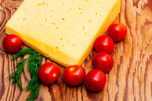 Cheese Greens And Cherry Tomatoes On A Cutting Board On The Table