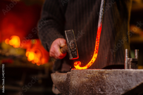 Leinwand Poster The blacksmith hits the red-hot workpiece in the forge with a hammer and glowing