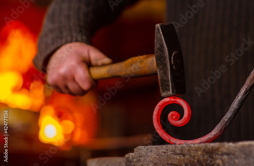 Fototapeta Close-up of the hands of a blacksmith twisting a spiral with a hammer, putting a red-hot iron blank on an anvil