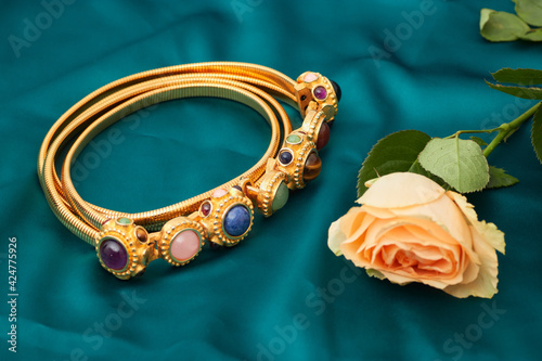 Fotografia, Obraz Vintage golden belt inlaid with jewels, flowers beside, on green background