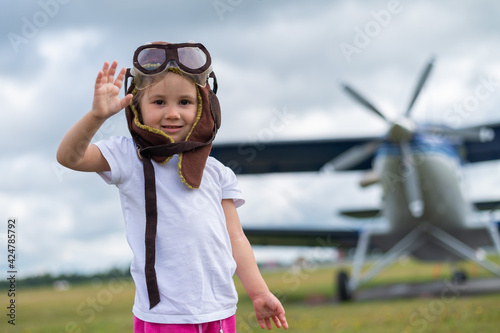 A cute little girl dressed in a cap and glasses of a pilot on the background of an airplane Wallpaper Mural