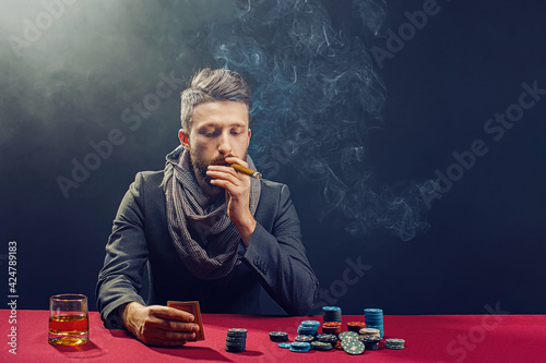 Stylish bearded Man in suit and scarf playing in dark casino Wallpaper Mural