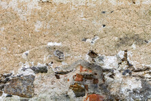 Old Damaged Dirty Wall With Cracks And Wholes. Ruin Facade Made Of Natural Stone And Bricks. A Vintage Background For Design