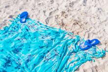 Blue Flipflops On Blue Beach Blanket Towel On White Sand.