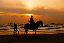 A Silhouette Of A Horse Riding A Horse On Hua Hin Beach, Thailand