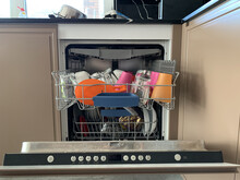 The Dishwasher Is Loaded With Dishes. Dishes In An Open Dishwasher. Kitchen Appliances For Dishes.