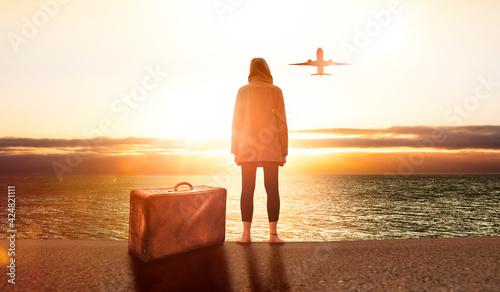 Leinwand Poster Junge Frau mit einem Koffer bei sonnenuntergang