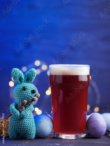 Fototapeta Creative Easter. A glass of craft beer, colored Easter pastel eggs, a bunny with a willow branch obraz na płótnie