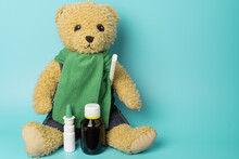 Cute Toy Bear Holding A Thermometer With Nasal Spray And Cough Syrup. Seasonal Cold And Flu Concept.