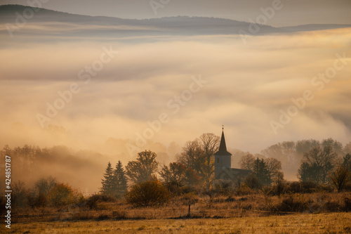 Fototapeta Picture with the motif of the Christian faith, the silhouette of the Christian church, the morning sun and the fog in the background