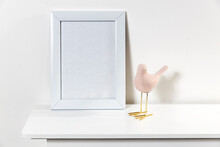 White Photo Frame With Blank Space.. Statuette Of A Pink Bird.