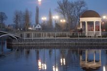 Gazebo On An Artificial Lake At Night. Reflection In The Water Of The Gazebo And The Glowing Lanterns. Ukraine, Kremenchug