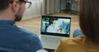 Doctor conducts online consultation for caucasian couple holding X-ray of lungs. Remote treatment appointment. View from screen.