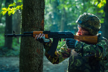 Sniper Soldier In Army Ammunition Camouflage And Helmet Holding Rifle And Aiming Tagret In Forest.