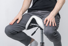 Young Man Sitting On A Saddle Chair. Perspective View