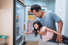 Portrait Of Asian Father Preventing Her Daughter To Take Some Food Inside The Fridge
