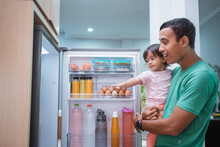 Toddler Asking For Some Food Inside The Refrigerator With Father