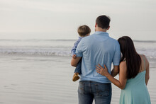 Family Of Three Standing On The Beach By The Ocean Looking Out Towards The Horizon, Coronado California