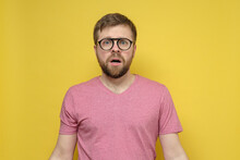 Frightened, Shocked Bearded Man With Glasses Looks At The Camera With Large Eyes And An Open Mouth. Yellow Background.