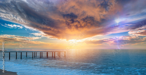 Fototapeta Old wooden jetty during stormy clouds on the Mediterranean sea with Thunderbolt strike  obraz