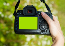 Hand Holds The Camera. Female Hands With A Camera, Holds To Photograph, Green Background. Close-up, Concept Of Tourism, Travel, Hobby, Blogger. Black Camera, Screen. Editorial, Ukraine, Kiev 2020