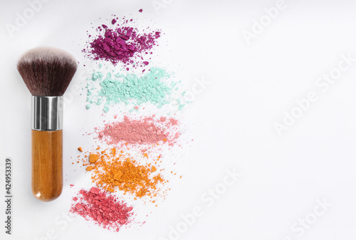 Fotografia, Obraz Makeup brush and scattered eye shadows on white background, flat lay