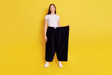 Full Length Photo Of Young Adult Caucasian Girl Wearing Casual T Shirt And Too Big Size Pants, Looks At Camera With Puzzled Expression And Bewilderment, Purses Lips, Isolated Over Yellow Background.