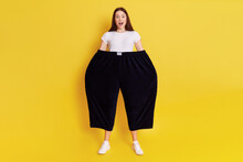 Shocked Astonished Woman Wearing Old Too Big Black Trousers Keeps Hands In Pants. Looks At Camera With Open Mouth And Big Eyes, Has Surprised Facial Expression, Posing Isolated Over Yellow Background.